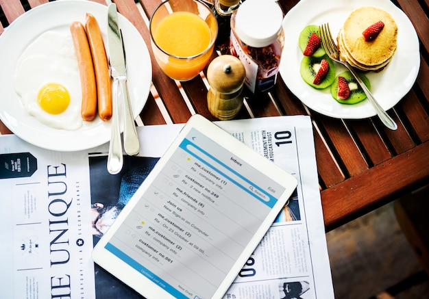 Primer plano de desayuno con tableta digital y periódico
