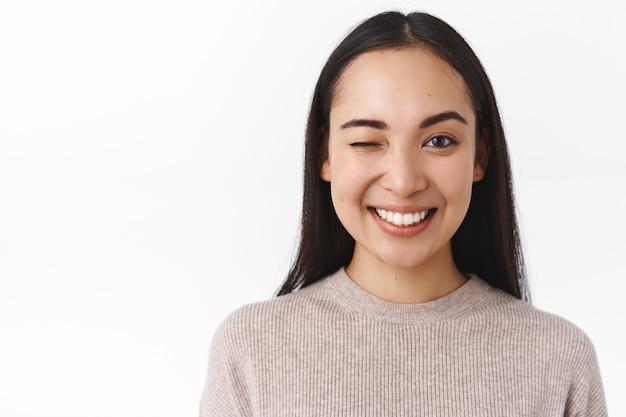 Primer plano descarado, entusiasta feliz sonriente mujer asiática con cabello largo y oscuro, maquillaje natural desnudo, tener un gran día, enviar vibraciones positivas, guiñar un ojo para animar a un amigo y decir todo bajo control