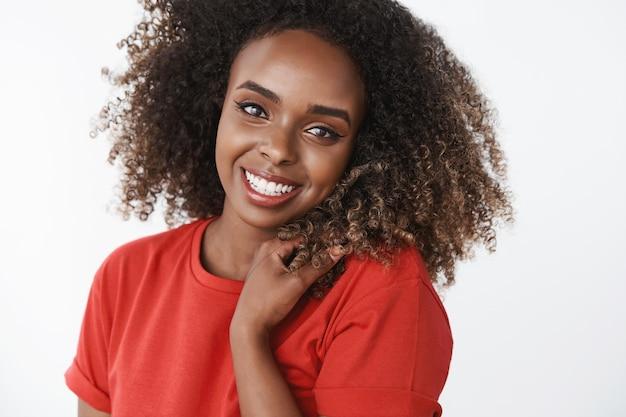 Primer plano de despreocupada, feliz y gentil hermosa modelo afroamericana con rizos sonriendo ampliamente tocando el cabello, mirando encantada, tierna al frente con camiseta roja sobre pared blanca