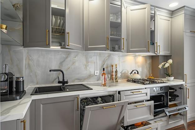 Primer plano de detalles de cocina clásica contemporánea gris y blanca diseñada en estilo moderno, todas las puertas y cajones de los muebles están abiertos