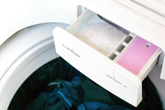 Primer plano del detergente y suavizante de telas en la lavadora.
