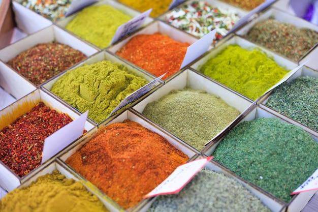 Primer plano de diferentes tipos de especias orientales coloreadas y condimentos en el mercado en formas cuadradas con etiquetas de precio