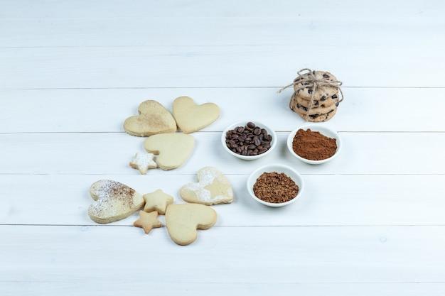 Primer plano de diferentes tipos de galletas con granos de café, café instantáneo, cacao sobre fondo de tablero de madera blanca. horizontal