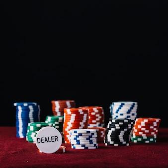 Primer plano del distribuidor y coloridas fichas de póquer apiladas en mesa roja