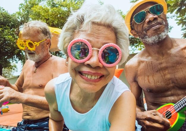 Primer plano de diversos adultos mayores sentados junto a la piscina disfrutando del verano juntos