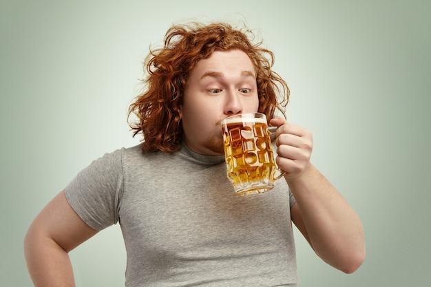 Primer plano de divertida pelirroja gorda hacer beber cerveza fría de vidrio