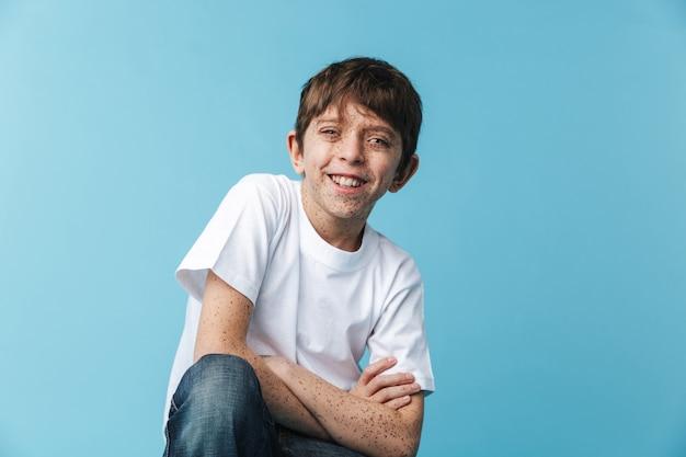 Primer plano de un divertido muchacho caucásico con pecas vistiendo camiseta blanca casual sonriendo aislado sobre pared azul