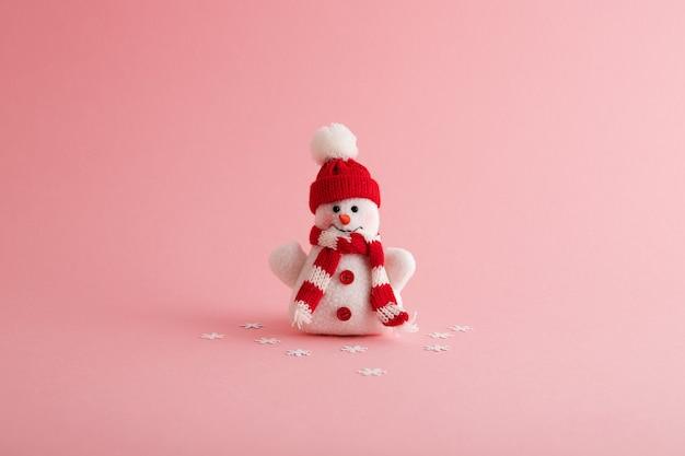Primer plano de un divertido muñeco de nieve y copos de nieve en el fondo rosa