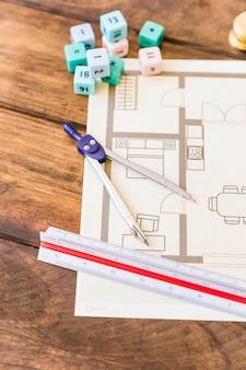 Primer plano de divisor, regla, bloques de matemáticas y planos en el escritorio de madera