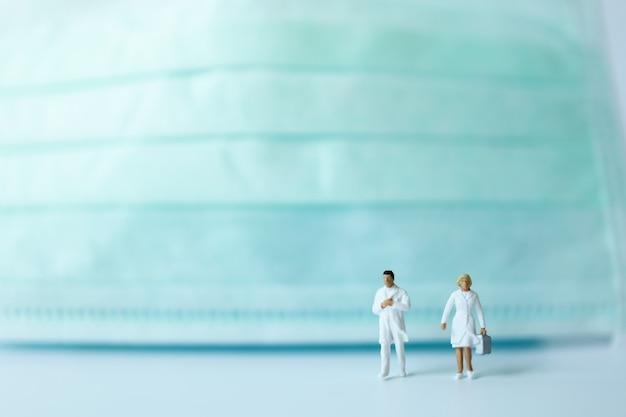 Primer plano de docter y enfermera figura en miniatura personas caminando con marca de rostro quirúrgico como fondo.