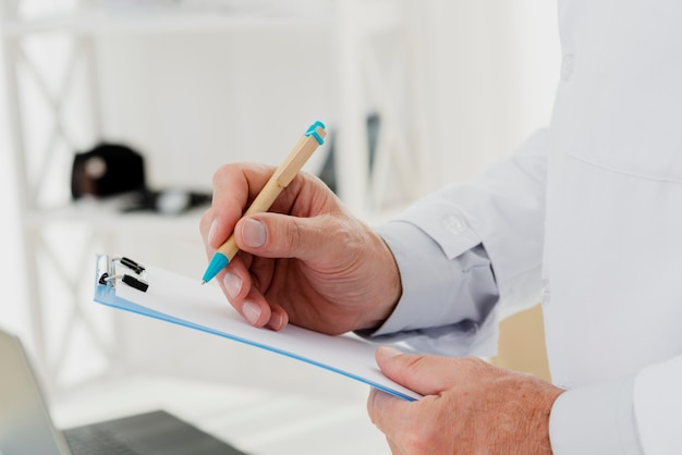 Primer plano del doctor escribiendo en portapapeles