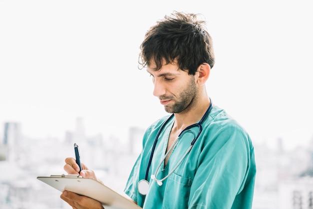 Primer plano de un doctor hombre escribiendo en portapapeles