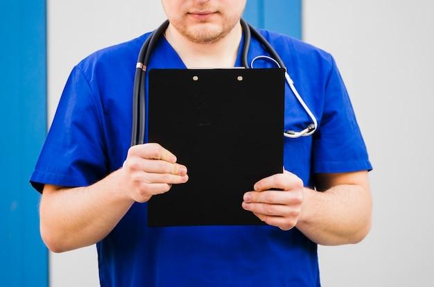 Primer plano de un doctor hombre sosteniendo portapapeles en la mano con estetoscopio alrededor de su cuello