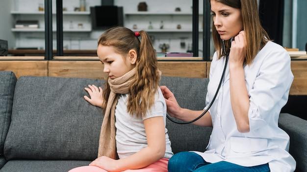 Primer plano de una doctora comprobando a la niña enferma con estetoscopio