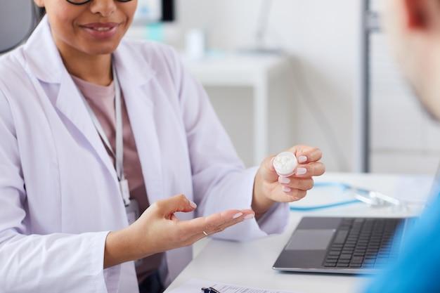 Primer plano de la doctora sosteniendo pastillas en la mano y recetárselas al paciente