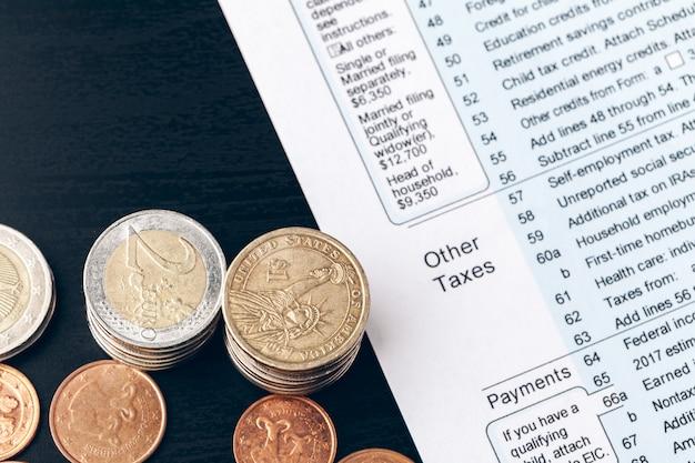 El primer plano de documentos contables con monedas de dinero
