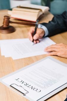 Primer plano de los documentos del contrato cerca del juez que examina documentos sobre el escritorio