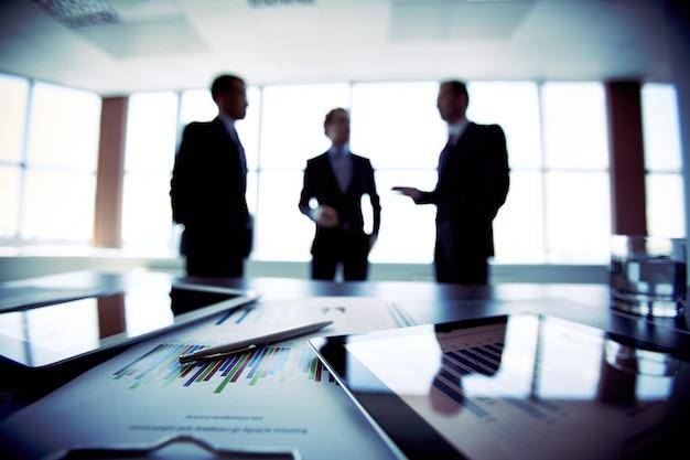 Primer plano de documentos con hombres de negocio borrosos de fondo
