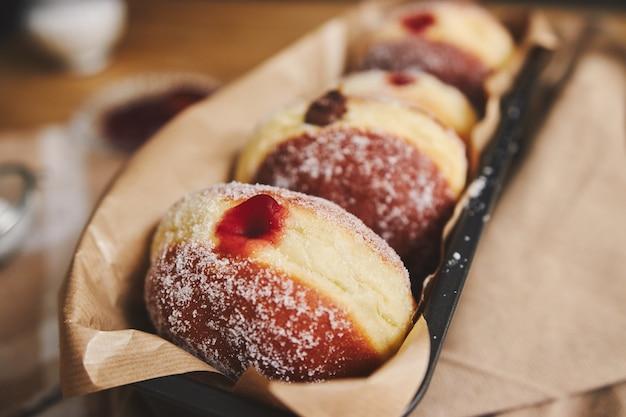 Primer plano de donuts esponjosos con mermelada en un recipiente bajo las luces