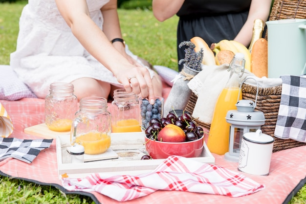 Primer plano de dos amigas disfrutando de la merienda en picnic
