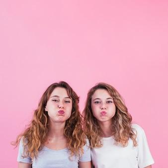 Primer plano de dos amigas soplando sus mejillas contra el fondo rosa