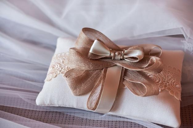 Primer plano de dos anillos de boda en una almohada roja