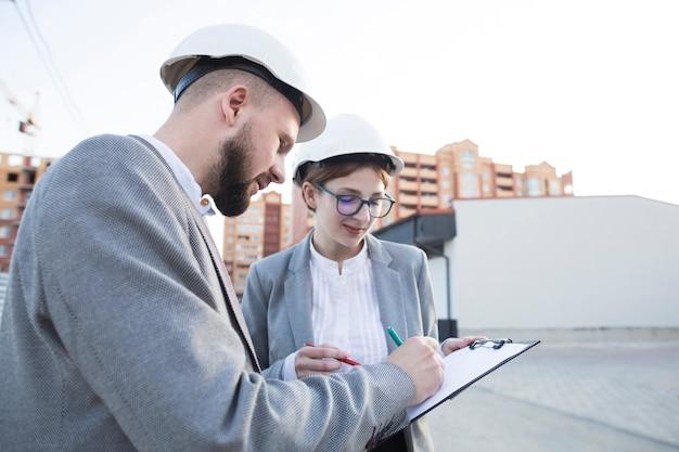 Primer plano de dos arquitectos trabajando juntos en el sitio de construcción
