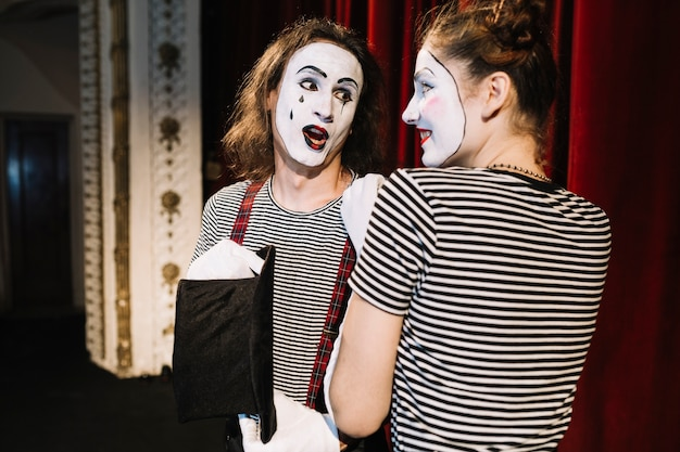 Primer plano de dos artistas mimos jóvenes actuando en el escenario