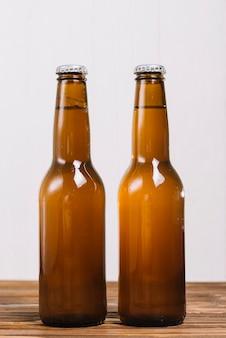 Primer plano de dos botellas de cerveza en la superficie de madera
