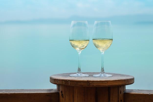 Primer plano de dos copas de vino blanco sobre la mesa en la terraza con vista al mar