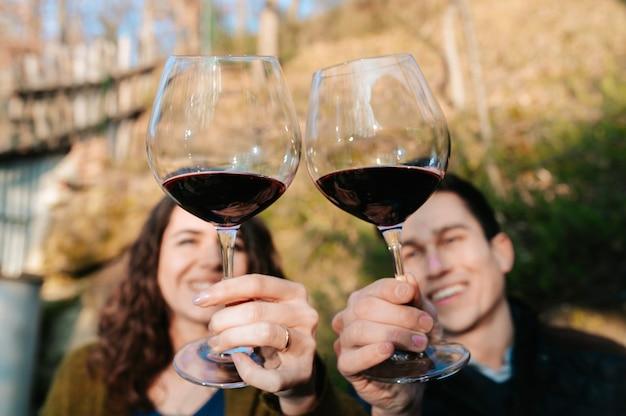 Primer plano dos copas de vino tinto con pareja sonriente en segundo plano. personas tomando un aperitivo al aire libre.
