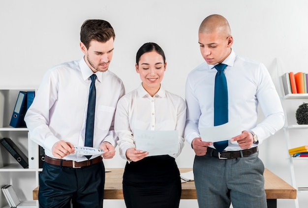 Primer plano de dos empresario y sonriente joven empresaria asiática mirando informe financiero