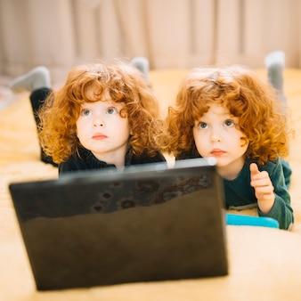 Primer plano de dos gemelos bonitos que mienten delante del ordenador portátil que mira para arriba