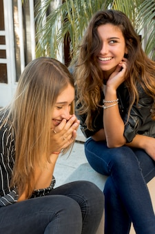 Primer plano de dos hermosas amigas riendo juntos