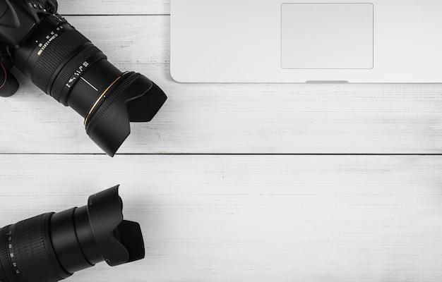 Primer plano de dos lentes de cámara con laptop en mesa de madera blanca