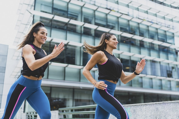 Primer plano de dos mujeres atractivas corriendo y haciendo ejercicios - concepto de fitness y deporte