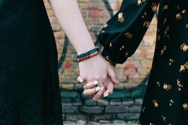 Primer plano de dos mujeres homosexuales lgbt pareja cogidos de la mano