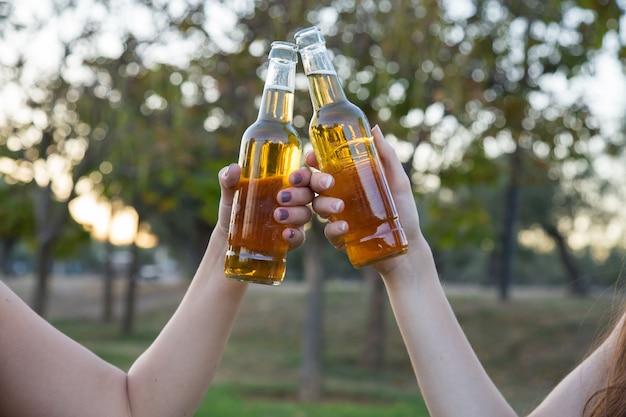 Primer plano de dos mujeres jóvenes brindando con botellas de cerveza divirtiéndose.