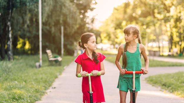 Primer plano de dos niñas montando patinete pateando mirando el uno al otro en el parque