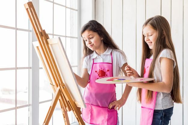 Primer plano de dos niñas de pie cerca de la pintura de la ventana en el caballete con pincel
