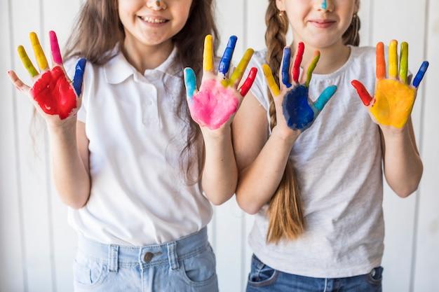 Primer plano de dos niñas sonrientes mostrando sus manos pintadas con color