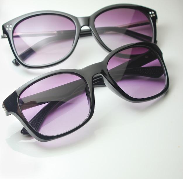 Primer plano de dos pares de gafas de sol en blanco