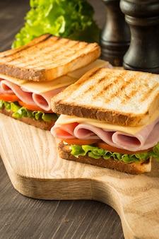 Primer plano de dos sándwiches con tocino, salami, jamón y verduras frescas en la tabla de cortar de madera rústica. concepto de club sandwich.