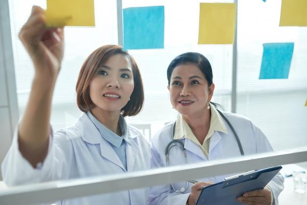 Primer plano de dos trabajadores médicos que ponen adhesivos memo en el tablero de vidrio