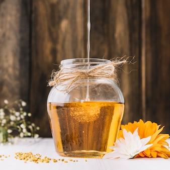 Primer plano de dulce miel goteando en frasco de vidrio con flores en el escritorio
