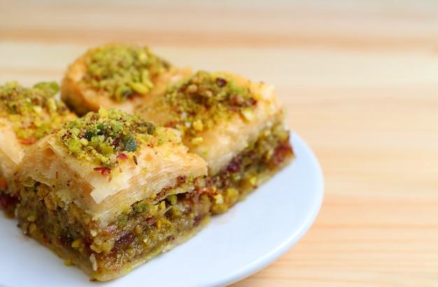 Primer plano de los dulces de baklava con nueces de pistacho servido mesa de madera