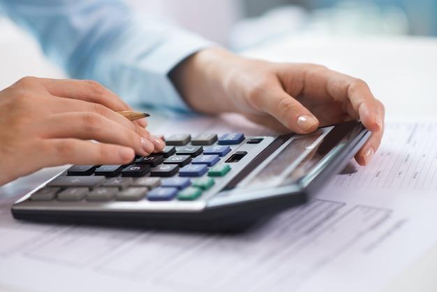 Primer plano de economista trabajando y contando datos en calculadora