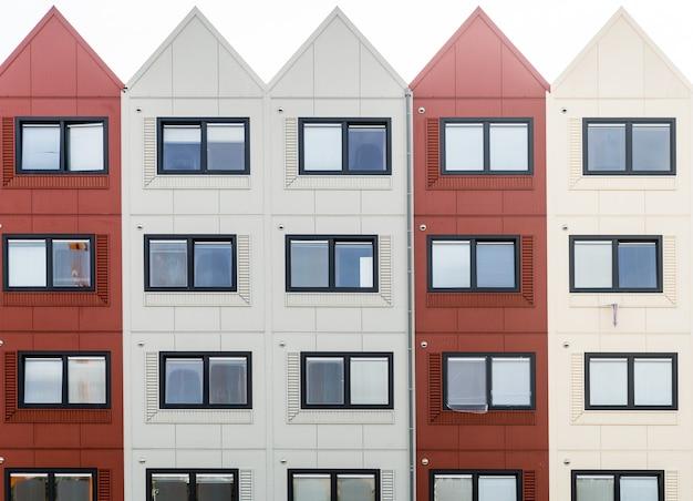 Primer plano de un edificio con secciones rojas y blancas y techos triangulares