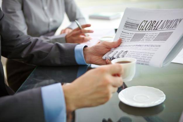 Primer plano de ejecutivo con un café y un periódico