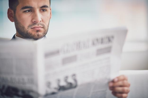Primer plano de ejecutivo concentrado leyendo una noticia